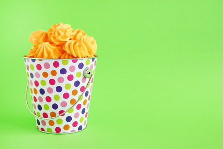 Small colorful bucket filled with yellow meringue on a green background. Minimal concept with copy space.