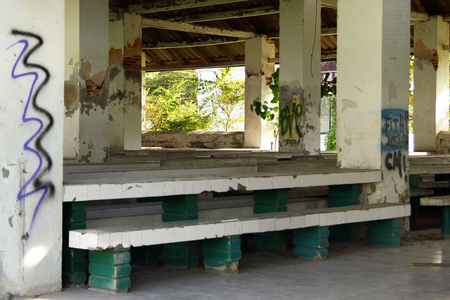 Chiang Mai, Thailand - December 25, 2017: Canteen with stones benches and tables in abandoned women prison.