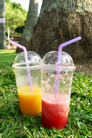 Two plastic glasses with mango juice and watermelon juice on a grass in a park. Stock Photo