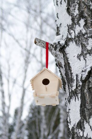 Wooden birdhouse on a branch of tree in winter snowy forest.
