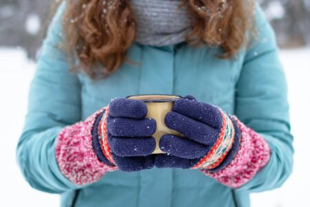 Woman's hands in knitting colorful gloves are holding metal cup with hot tea in winter park. Foto de archivo