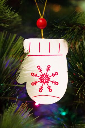 Wooden mitten with red Christmas ornament on a fir tree with Christmas decorations and blurred lights.