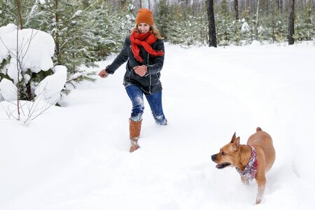Young woman is playing with her dog on a walk in winter coniferous forest.