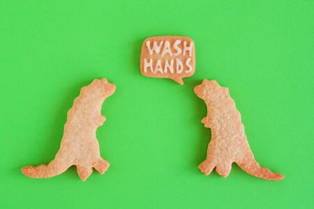 Two homemade cookies in shapes of dinosaurs with inscription 'Wash hands' on green background, top view. Sweet shortbread with white glaze. Social distancing concept.