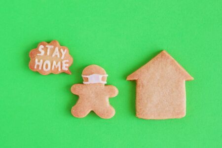 Homemade shortbread cookies with white glaze on green background, top view. Man in face mask and with callout with inscription 'Stay home' near his house. Social distancing concept.