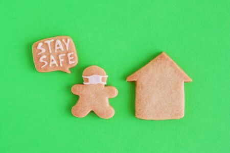 Homemade shortbread cookies with white glaze on green background, top view. Man in face mask with callout with inscription 'Stay safe' near his house. Social distancing concept.