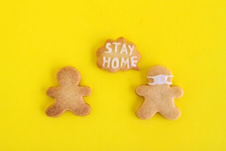 Homemade shortbread cookies with white glaze on yellow background, top view. Two men one of them in face mask and with callout cloud with text 'Stay home'. Foto de archivo