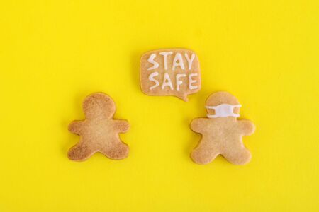Homemade shortbread cookies with white glaze on yellow background, top view. Two men one of them in face mask and with callout cloud with text 'Stay safe'.