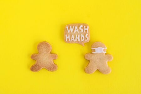 Homemade shortbread cookies with white glaze on yellow background, top view. Two men one of them in face mask and with callout cloud with text 'Wash hands'.
