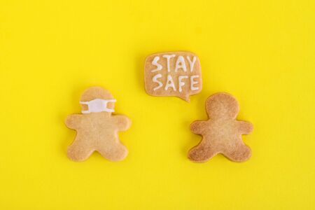 Homemade cookies in shapes of people with inscription 'Stay safe' and with face medical mask on yellow background, top view. Sweet shortbread with white glaze. Social distancing concept.