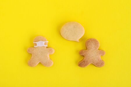 Homemade cookies in shapes of people with callout cloud and with face medical mask on yellow background, top view. Sweet shortbread with white glaze. Social distancing concept. 写真素材
