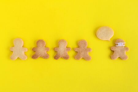 Homemade shortbread cookies with white glaze on yellow background, top view. Crowd of people and one man in face mask and with callout cloud.