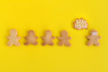Homemade cookies in shapes of people with inscription 'Stay home' and with face medical mask on yellow background, top view. Sweet shortbread with white glaze. Social distancing concept. 写真素材