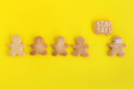 Homemade shortbread cookies with white glaze on yellow background, top view. Crowd of people and one man in face mask and with callout cloud with text 'Stay safe'