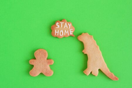 Homemade cookies in shapes of dinosaur and man with inscription 'Stay home' on green background, top view. Sweet shortbread with white glaze. Social distancing concept.