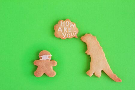 Homemade shortbread cookies in shapes of dinosaur and man in face mask and with callout cloud with text 'How are you?' on green background. Social distancing concept.