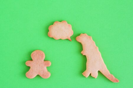 Homemade shortbread cookies in shapes of dinosaur and man with callout cloud on green background, top view. Stock Photo