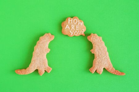 Homemade shortbread cookies in shapes of dinosaurs with callout cloud with text 'How are you?' on green background, top view.