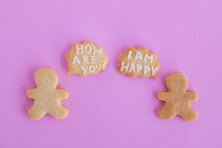 Homemade shortbread cookies with white glaze on pink background, top view. Two people with callout cloud with text 'How are you?' and 'I am happy'