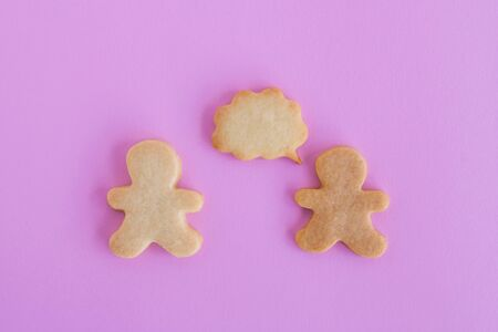 Homemade shortbread cookies on pink background, top view. Two people with callout bubble blank message.