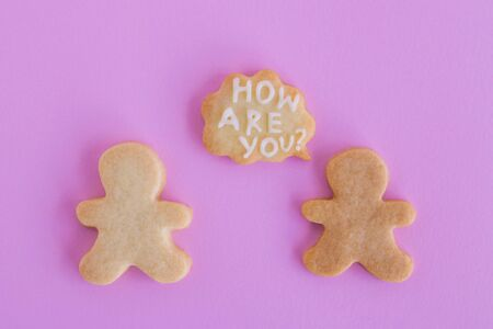 Homemade shortbread cookies with white glaze on pink background, top view. Two people with callout cloud with text 'How are you?' 写真素材
