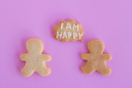 Homemade shortbread cookies with white glaze on pink background, top view. Two people with callout cloud with text 'I am happy' 写真素材