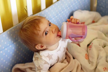 Cute one year old girl with blue eyes and blond is drinking water from bottle after waking up in the morning in her bed.