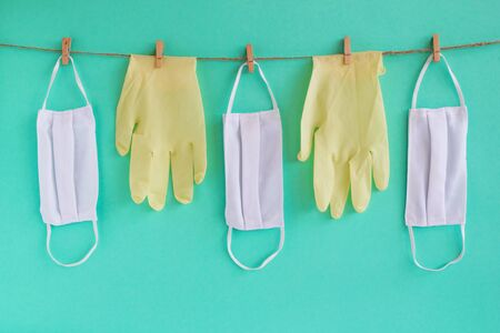 Drying of medical face masks and disposable medical gloves after washing on a rope for reuse, on a turquoise background. Concept of new normal lifestyle. Stok Fotoğraf