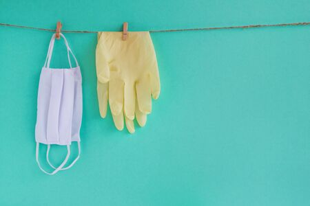 Drying of medical face masks and disposable gloves after washing on a rope for reuse, on a turquoise background with copy space. Concept of new normal lifestyle. Stok Fotoğraf