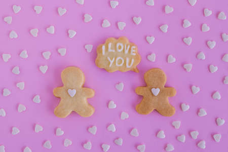 Homemade shortbread cookies decorated white glaze. Two people with callout cloud with text 'I love you' on pink background with heart sprinkles, top view
