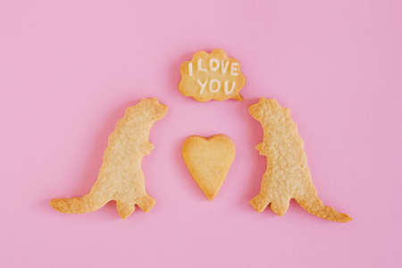 Homemade shortbread cookies with white glaze on pink background, top view. Two dinosaurs with callout cloud with text 'I love you'
