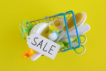 Flat lay on shopping basket with baby care items - scissors, hairbrushes, pacifiers, thermometer, cotton pads, pacifier holders and nasal aspirator - on yellow background with paper price tag with text 'Sale'.
