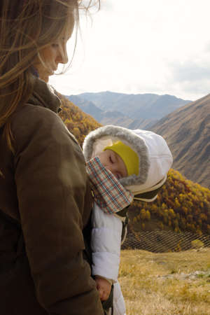 Portrait of young beautiful woman with her little sleeping daughter in ergo carrier on a background of autumn mountains. Caucasus Mountains, Georgia.