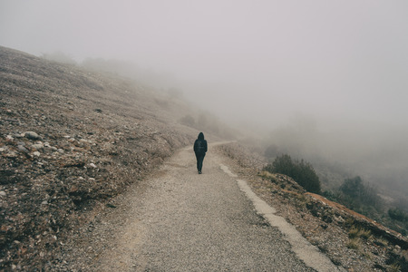 Girl walking on her back on a mountain road with a lot of fog