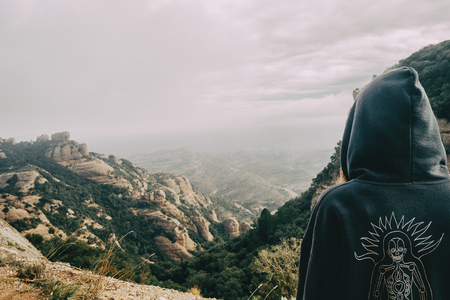 Girl on her back with a hood looking at a landscape of mountains on a day with clouds Stok Fotoğraf