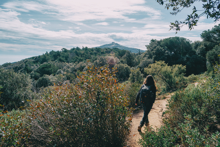 Woman walking in the distance on a trail among mountains on a sunny day