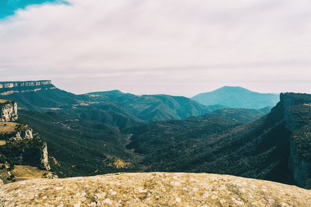 A vast expanse of fields and mountains full of trees taken from the top of a cliff Stok Fotoğraf