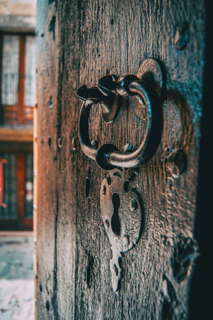 A lock and a handle of a medieval wooden door captured from the side with the villages street in the background