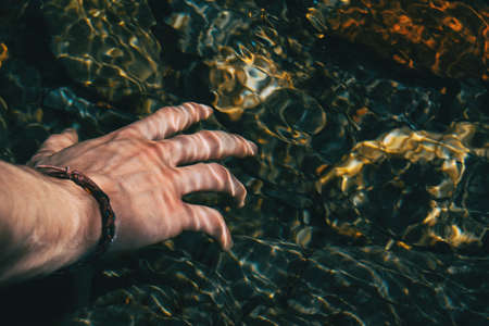 Close-up of a hand touching the surface of the water with light reflections in nature