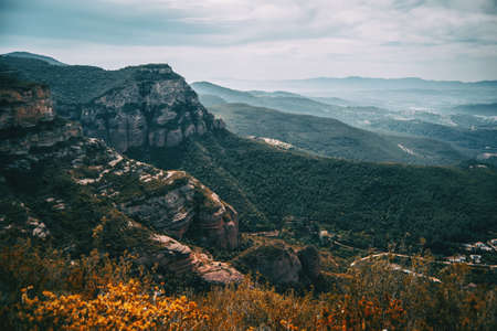 An imposing landscape of rugged mountains and fields that extend to the horizon in Sant Miquel del Fai 스톡 콘텐츠