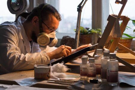 The master restorer in a white coat and respirator restores the icon, the restorer works in his restoration workshop