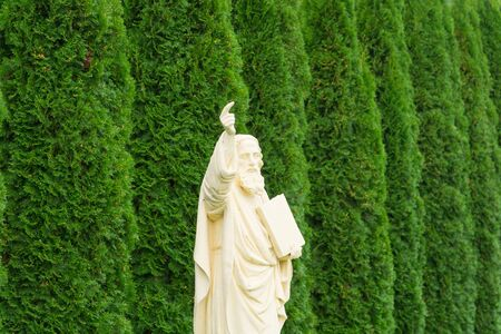 White statue of the apostle Paul, a figure with a raised right hand with a raised index finger and with a book in his left hand against a background of large green thuja trees Stok Fotoğraf