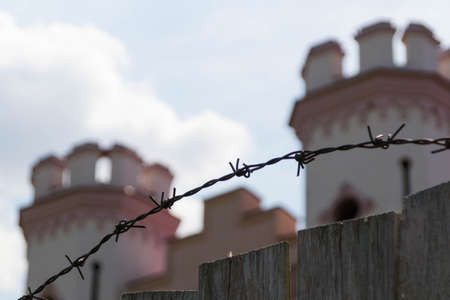 A wooden fence and barbed wire enclose an ancient palace in the medieval gothic style, which is under restoration Editorial