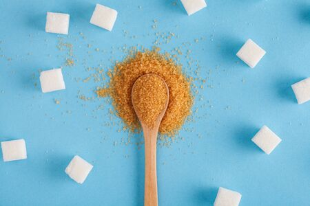 different types of sugar, brown sugar in wooden spoon and white sugar cubes on pastel blue background, top view, flat lay