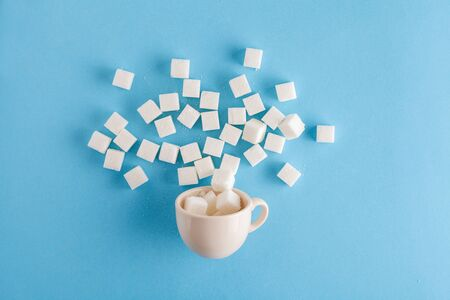 coffee cup full of sugar cubes isolated on pastel blue background, hidden sugar in sweet drinks, diabetes risk, studio shot, top view, flat lay