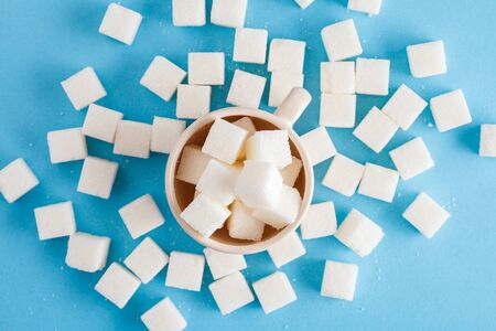 coffee cup full of sugar cubes isolated on pastel blue background, hidden sugar in sweet drinks, diabetes risk, studio shot, top view, flat lay Banco de Imagens