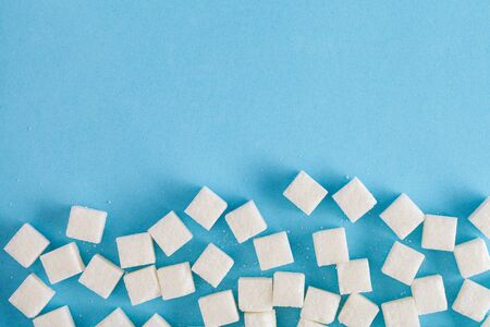 sugar cubes on pastel blue background, flat layout, top view, copy space