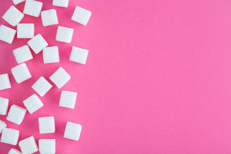 sugar cubes on vivid pink background, flat layout, top view, copy space
