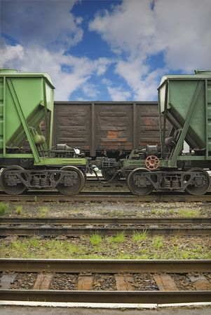 Cargo railway station. Three old railway cars for loose and common cargo are staying on the middle railways. There is a small summer rain. photo