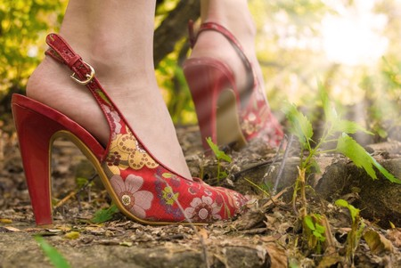 Pair of female feet high-heeld on red shoes. Woman stands on stone staircase. She meets a dawn in the wood.